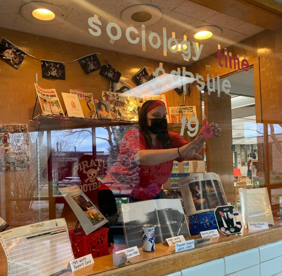 Junior Annabel Holland preps the library display with artifacts from the 1985 time capsule.